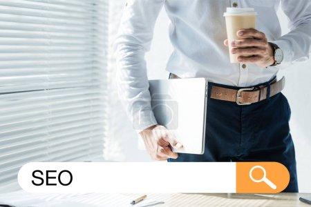 cropped view of developer holding laptop and coffee to go, with SEO search bar
