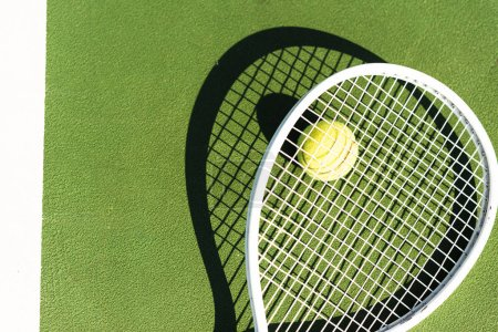 top view of tennis racket and ball lying on green tennis court