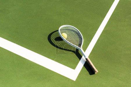 Photo pour Gros plan sur une raquette de tennis et balle gisant sur un court de tennis vert - image libre de droit