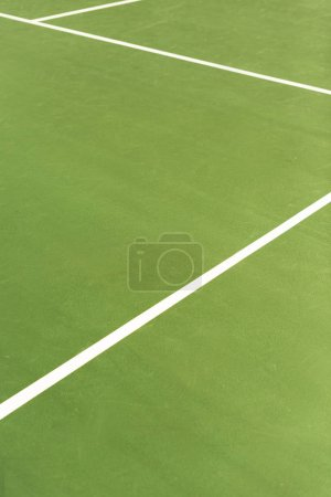 close up view of green tennis court with white lines background