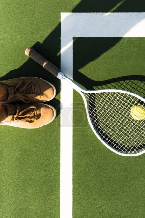 partial view of female tennis player standing near tennis racket and ball on court