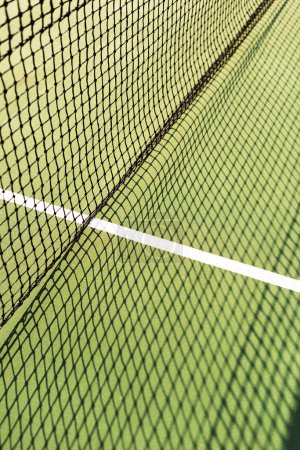 close up view of net with shadow on green tennis court