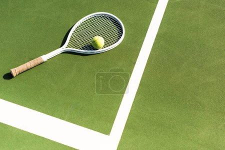 close up view of tennis racket and ball lying on green tennis court