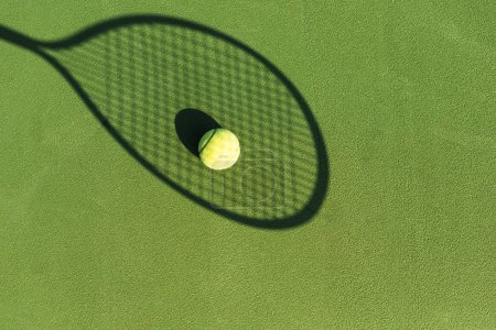 top view of tennis ball and tennis racket shadow on green tennis court