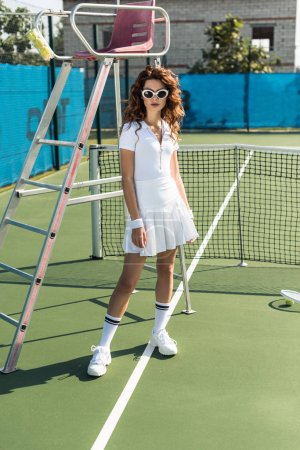 beautiful woman in white tennis uniform and sunglasses posing on tennis court