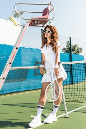 fashionable woman in white tennis uniform and sunglasses with racket and ball leaning on referee chair on tennis court