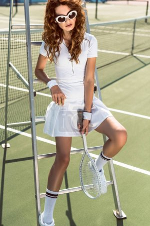 stylish woman in white tennis uniform and sunglasses with racket and ball leaning on referee chair on tennis court