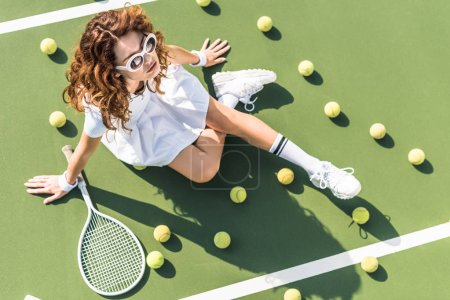 Photo for Overhead view of fashionable tennis player in white sportswear and sunglasses resting on tennis court with balls and racket near by - Royalty Free Image