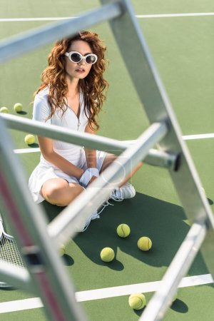 female tennis player in stylish white sportswear and sunglasses sitting on tennis court with balls around