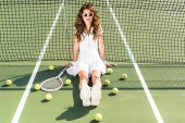 young fashionable tennis player in white sportswear and sunglasses sitting at net with tennis equipment around on tennis court