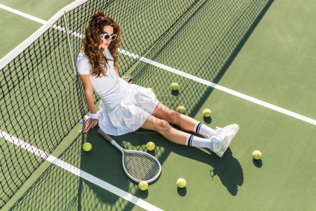 high angle view of stylish tennis player in white sportswear and sunglasses sitting at net with tennis equipment around on tennis court