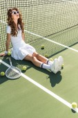 young beautiful tennis player in white sportswear and sunglasses sitting at net with tennis equipment around on tennis court