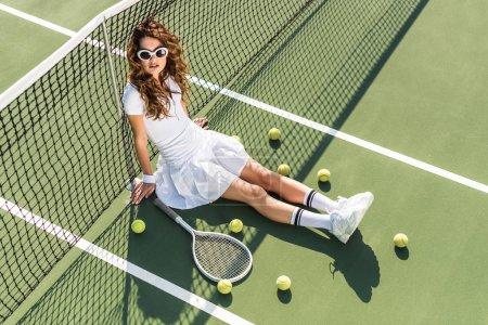 Photo pour Vue d'angle élevé de jeune tennisman élégant dans des vêtements de sport blanc et lunettes de soleil assis au net avec équipement de tennis autour sur un court de tennis - image libre de droit