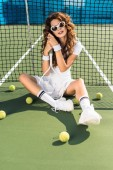 beautiful tennis player in sunglasses with tennis racket sitting at tennis net on tennis court