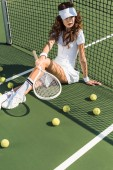 stylish tennis player in white sportswear with tennis racket sitting at net on tennis court