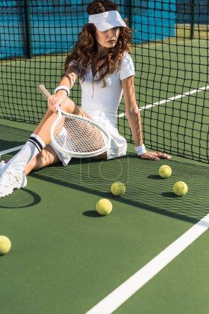 beautiful tennis player in white tennis uniform with racket sitting near tennis net on court with tennis balls around
