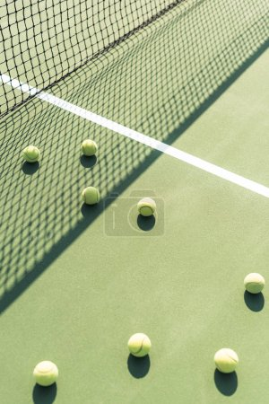 close up view of tennis balls and net on tennis court