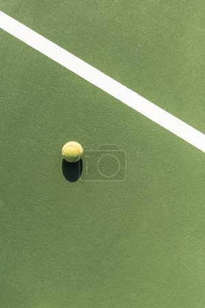 top view of tennis ball on green tennis court