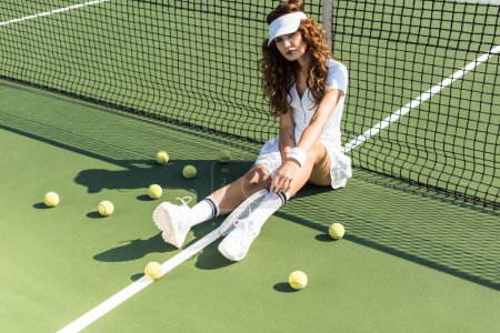 beautiful tennis player in stylish sportswear with racket sitting near tennis net on court with tennis balls around
