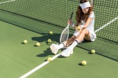 beautiful female tennis player with racket sitting near tennis net on court with tennis balls around