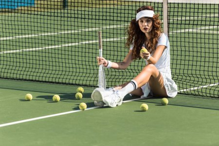 beautiful female tennis player with racket sitting near tennis net on court with tennis balls around