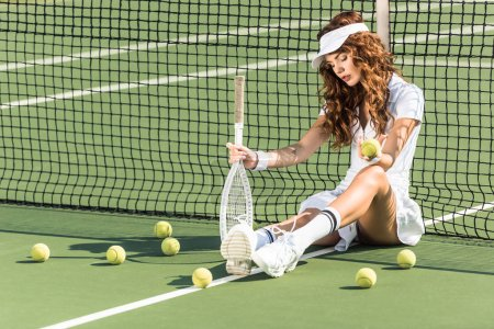 Photo for Beautiful female tennis player with racket sitting near tennis net on court with tennis balls around - Royalty Free Image