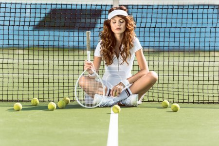 beautiful female tennis player with racket and eyes closed sitting near tennis net on court with tennis balls around