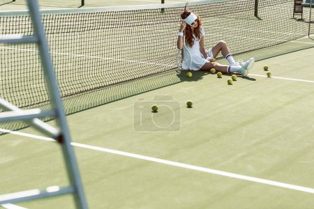 stylish female tennis player in sunglasses resting near net on tennis court with equipment near by