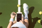 overhead view of female tennis player with racket taking picture of herself on tennis court