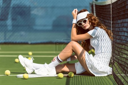 fashionable female tennis player in sunglasses resting near net on tennis court with equipment near by