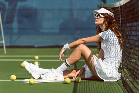 side view of fashionable female tennis player in sunglasses resting near net on tennis court with equipment near by