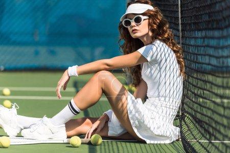Photo pour Vue latérale de la joueuse de tennis à la mode dans les lunettes de soleil se reposer près de filet sur un court de tennis avec équipement près de - image libre de droit