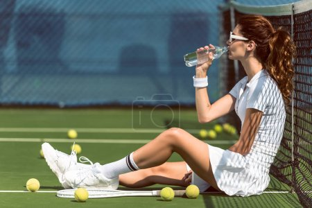 side view of beautiful tennis player in white tennis uniform and sunglasses drinking water while resting on court with racket and balls