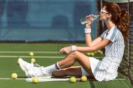 beautiful tennis player in white tennis uniform and sunglasses drinking water while resting on court with racket and balls