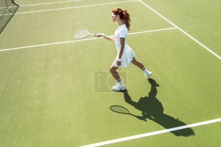 Photo for Side view of young attractive woman in white tennis uniform playing tennis on court - Royalty Free Image