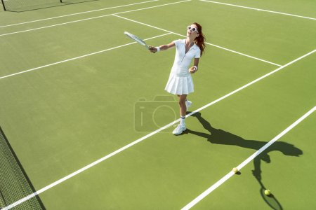 side view of young attractive woman in white tennis uniform playing tennis on court