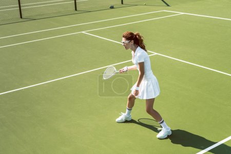young female tennis player in sunglasses playing tennis on court