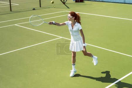 Photo for Young female tennis player in sunglasses playing tennis on court - Royalty Free Image