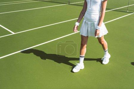 cropped shot of female tennis player in white sportswear walking on tennis court