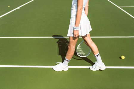 partial view of female tennis player in white sportswear with racket on tennis court