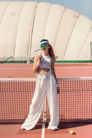 stylish woman in white clothing and cap with tennis racket posing at tennis net on court