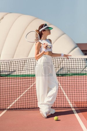 beautiful woman in white clothing and cap with tennis racket posing at tennis net on court
