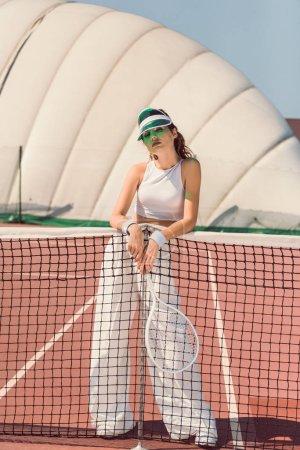 Photo pour Femme à la mode en vêtements blancs et casquette avec raquette de tennis posant au filet de tennis sur le court - image libre de droit
