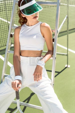 portrait of young woman in stylish white clothing and cap posing on referee chair on tennis court