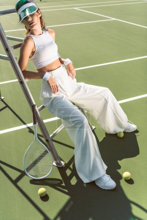 young woman in stylish white clothing and cap posing on referee chair on tennis court