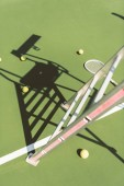 close up view of metal referee chair , tennis racket and balls on green tennis court