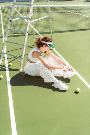 side view of young woman in stylish white clothing and cap tying shoelaces on tennis court with racket and balls