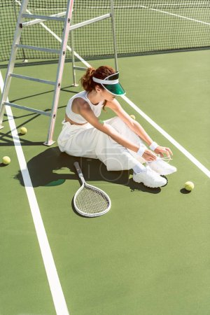 young woman in stylish white clothing and cap tying shoelaces on tennis court with racket and balls