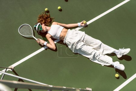 high angle view of stylish woman in white clothing and cap lying with racket lying on tennis court with racket