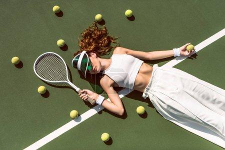 Photo pour Vue aérienne d'une femme élégante en vêtements blancs et une casquette couché avec une raquette allongée sur un court de tennis avec une raquette - image libre de droit
